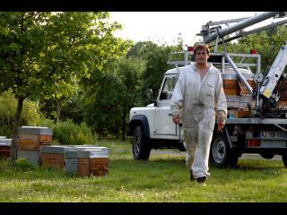 Un apiculteur en tenue s'approche de la caméra, derrière lui, un camion et des ruches