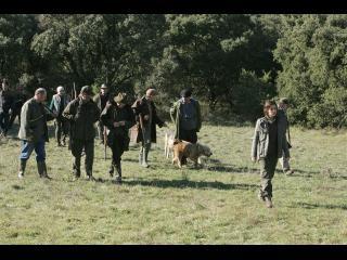 Un groupe de chasseurs accompagnés de leurs chiens sortent d'une forêt