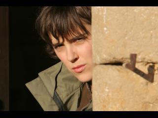 Un jeune homme guette quelque chose au loin, à moitié caché derrière un mur
