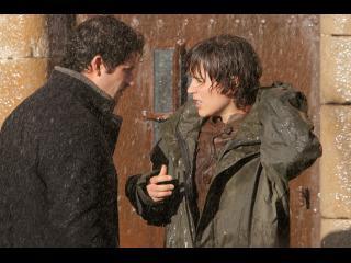 Un jeune homme et un homme parlent sous la pluie