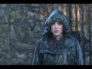 Une jeune femme, em imperméable bleu nuit est sous la pluie