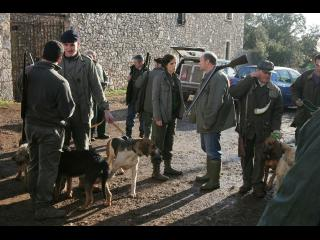 Un groupe de chasseurs armés et leurs chiens discutent devant une maison en pierre