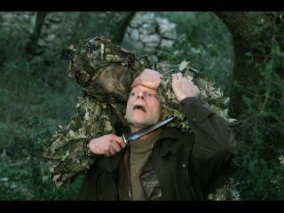 Un homme en tenue de camouflage tient un couteau sous la gorge d'un autre homme, à genous devant lui