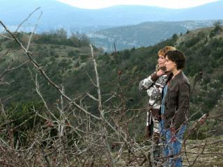 Deux femmes sont au milieu de montagnes verdoyantes, elles regardent au loin