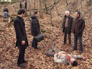 Quatre hommes sont dans la forêt autour d'un cadavre gisant au sol, sur un tapis de feuilles mortes