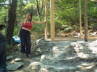 Une jeune fille est appuyée contre un pilier en bois, dans la forêt