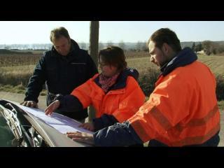 Une femme et deux hommes en tenue de travail étudient une carte déplié sur le capot d'une voiture