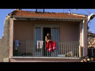 Une personne est appuyée sur la rambarde d'un balcon, devant une porte-fenêtre
