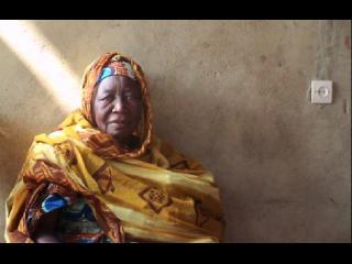 Une femme d'origine africaine, vêtue de couleurs vives, est assise contre un mur