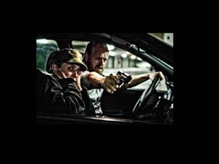 Un homme et une femme habillés en militaire sont dans une voiture, l'homme, au volant, tire par la fenêtre de la femme