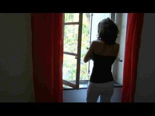 Une jeune femme regarde par une fenêtre, elle est dos à la caméra