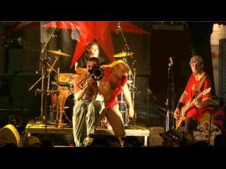 Sur une scène, une groupe de musique joue, au premier plan, un trompettiste
