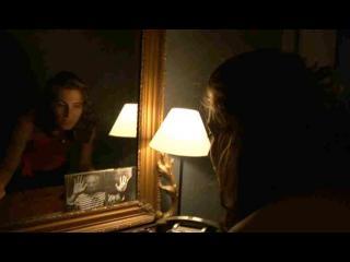 Une jeune femme regarde une photo de Picasso posée en bas d'un miroir, dans une chambre à peine éclairée par une lampe de chevet