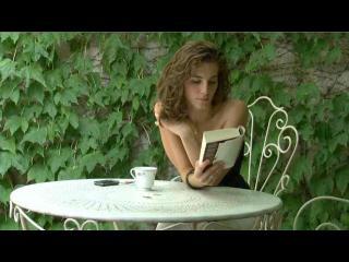 Une jeune femme aux épaules dénudées lit un livre assise à une table de jardin, derrière elle, un mur recouvert de lierre