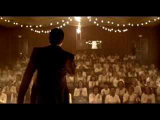 Un homme, de dos, fait un discours à des dizaines de personnes, habillées en costume de détenus