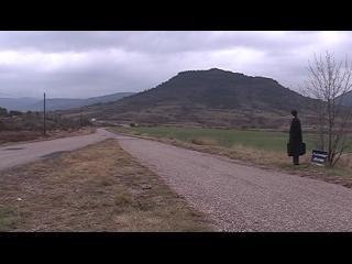 Au loin, une personne habillée en noir portant une mallette noire, attend debout au bord d'une route de campagne, au milieu des montagnes