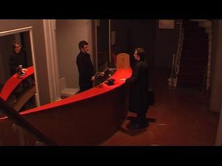 Deux hommes sont face à face, un comptoir rouge les sépare, un miroir est placé derrière l'un d'entre eux, la scène se reflète à l'intérieur de celui-ci