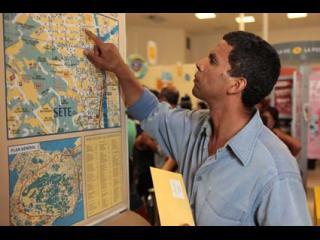 Homme cherchant à se repérer sur une carte de Sète accrochée à un mur
