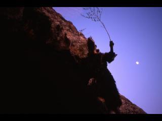 Photo nocturne de la pleine lune derrière une montagne