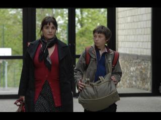 Une femme et un jeune adolescent marchent dans le hall d'entrée d'un immeuble