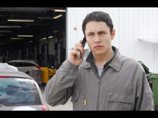 Jeune homme téléphonant devant un garage automobile