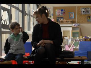 Femme parlant avec un petit garçon dans une salle de classe