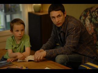 Adolescent et petit garçon assis autour d'une table basse