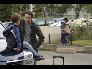 Petit garçon assis sur le capot avant d'une voiture, parlant avec un adolescent