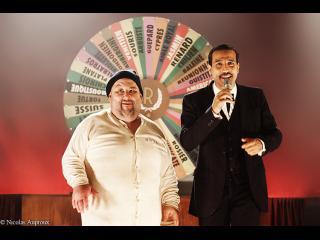 Un homme d'une certaine corpulence portant un costume de détenu et un homme en costume cravate avec un micro à la main, se trouvent devant une roue (type roue de la fortune)