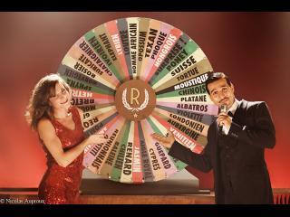 Un homme en costume cravate portant un micro et une jeune femme en robe rouge présentent la roue (Type roue de la fortune)