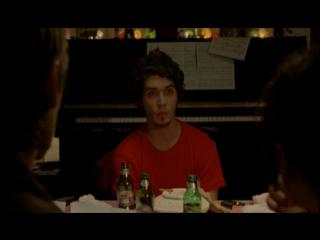 Un jeune homme est assis à table en face de deux personnes, devant lui, des bouteilles de bière vides