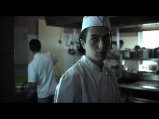 Jeune cuisinier dans la cuisine d'un restaurant