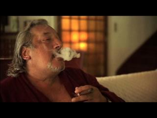 Homme (Jean-Claude Dreyffus) assis sur un canapé, fumant une cigarette