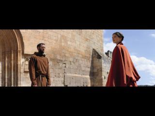 Devant la porte en pierre d'une château-fort, un moine (Vincent Cassel) regarde fixement une femme de la noblesse qui se trouve face à lui