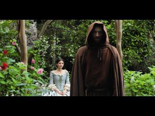 Femme de la noblesse assise dans un parc tandis qu'un moine (Vincent Cassel) lui tourne le dos (marchant vers l'objectif de l'appareil photo)