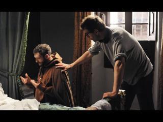 Moine (Vincent Cassel) agenouillé au pied d'un lit, priant. Un homme lui pose la main sur l'épaule