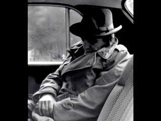 Photo en noir & blanc d'un homme portant un impair beige et un chapeau, endormi à l'arrière d'une voiture