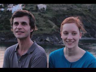 Un homme est une femme sont côte à côte, derrière eux, une étendue d'eau et une montagne