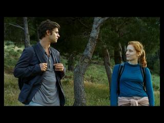 Un homme et une femme se baladent, équipés de sacs à dos, dans une forêt