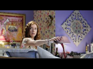 Femme renversant volontairement un verre de vin rouge sur un canapé