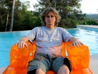 Homme dans un fauteuil gonflable orange, dans une piscine