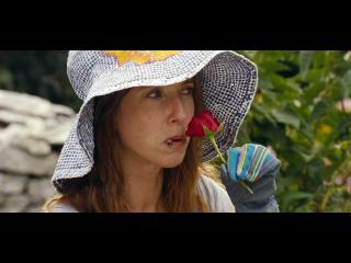 Femme portant un chapeau, sentant une rose rouge