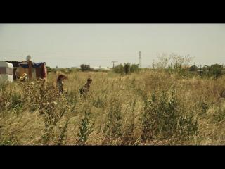 Deux personnes s'éloignent d'une caravane dans un espace inoccupé
