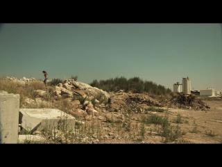 Une jeune fille rom marche à travers un paysage de ruines