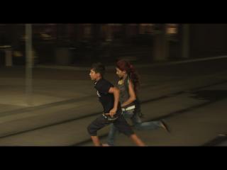 Une jeune fille et un jeune homme roms courent dans les rues de Montpellier
