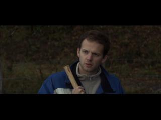 Un homme tenant un manche en bois dans la main droite regarde au loin l'air préoccupé