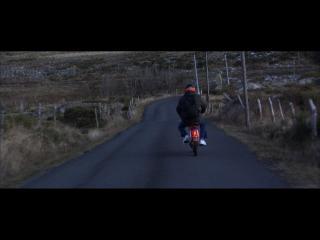 Un homme sur une motocyclette s'éloigne, sur une route de campagne bordée de champs à l'herbe jaunie