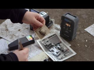 Des mains répertorient des objets vestiges de la mine, posés au sol