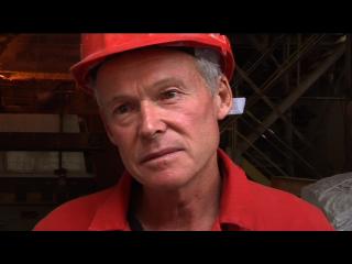 Un ouvrier portant sa tenue de travail, rouge, et un casque de la même couleur