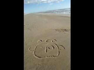 """À la plage, sur le sable, il est écrit le mot """"Ned"""" sous lequel figure le tracé d'un visage"""